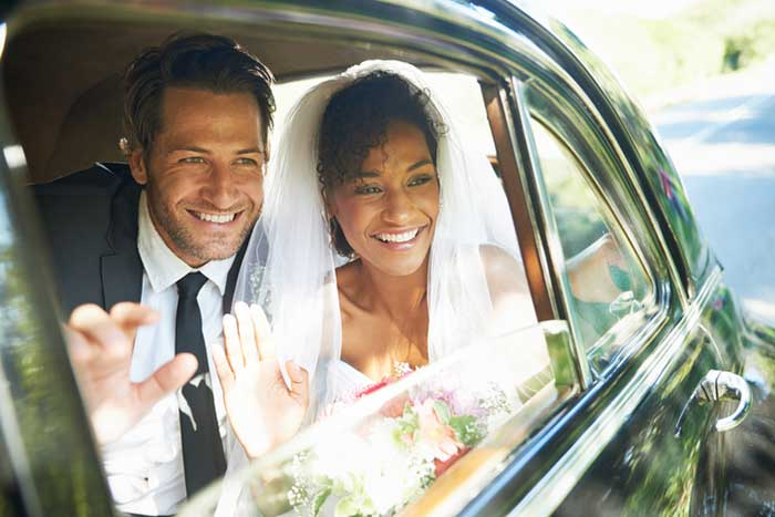 newlywed couple looking out the window of a car and waving