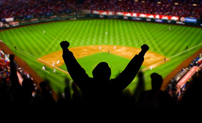 A baseball fan raises his arms in celebration.