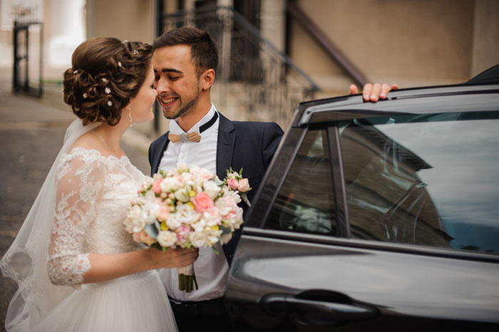 groom opens the door of the wedding car,intending to kiss the bride